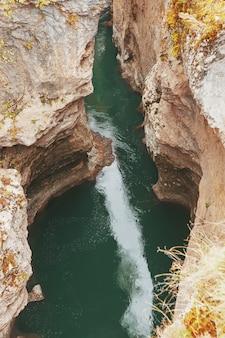 Desfiladero con un río de montaña con un agua turquesa vibrante entre las rocas.