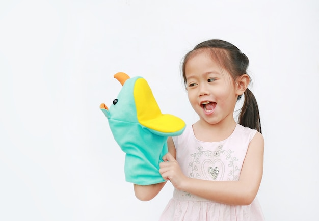 Desgaste asiático sonriente de la mano de la muchacha y jugando a las marionetas del rinoceronte en el fondo blanco.