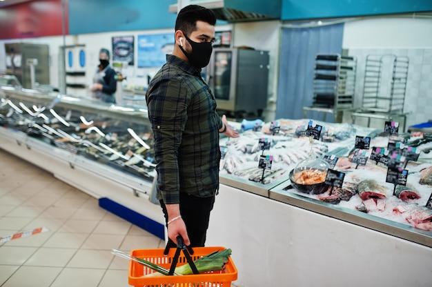 Desgaste del hombre asiático en compras de la mascarilla protectora en el supermercado durante la pandemia. elija mariscos.
