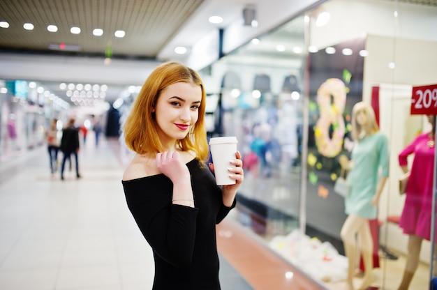 Desgaste de la muchacha pelirroja de moda en vestido negro con maquillaje brillante sosteniendo una taza de café en el centro comercial
