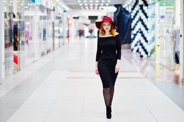 Desgaste de la muchacha pelirroja de la moda en el vestido negro y el sombrero rojo presentados en el centro comercial.