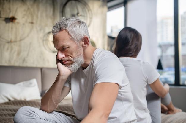 Desgracia, relación. infeliz hombre barbudo de pelo gris con la cabeza apoyada en la mano sentada espalda con espalda de mujer en casa