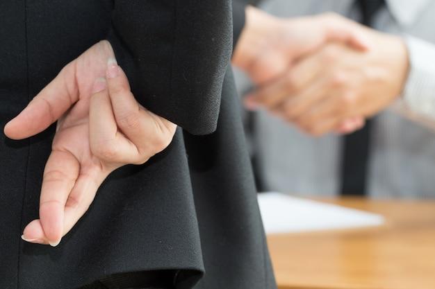 Deshonestidad, concepto de fraude empresarial, empresario mostrando los dedos cruzados