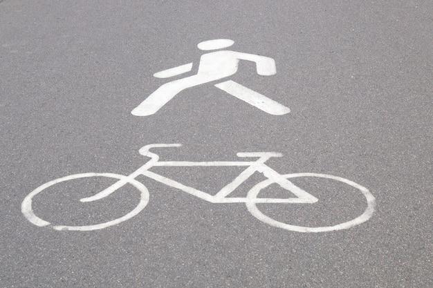 Designación de un carril para bicicletas y un camino peatonal pintado en pintura blanca sobre asfalto
