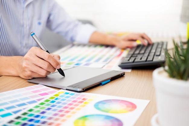 Designer editor en el trabajo, dibujando un nuevo proyecto en tableta gráfica y paleta de colores