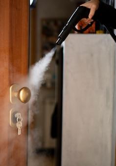 Desinfección y desinfección con vapor en casa, el flujo de vapor se dirige a la manija de la puerta y las llaves en la cerradura.