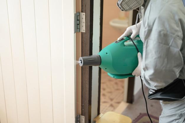 Desinfección de la oficina para prevenir covid-19, persona con traje blanco de materiales peligrosos con desinfección en la oficina, concepto de coronavirus