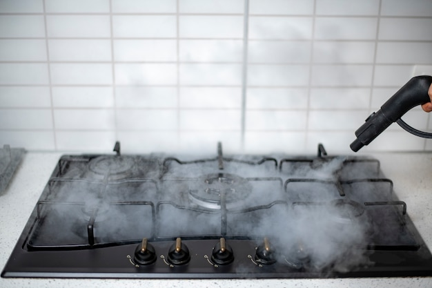 Desinfección con vapor y sanitización de la casa, tratamiento con vapor de la estufa de gas de la cocina.