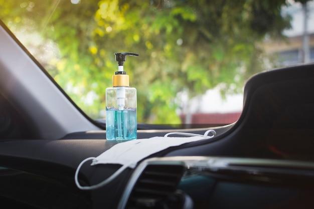 Desinfectante en gel para manos y mascarilla quirúrgica colocados en la consola del automóvil dentro de un automóvil