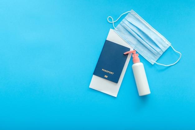 Desinfectante de máscara médica protectora y pasaporte de avión. concepto de vacaciones vuelos seguros durante el bloqueo de covid y coronavirus. lay flat sobre fondo de color azul con espacio de copia.