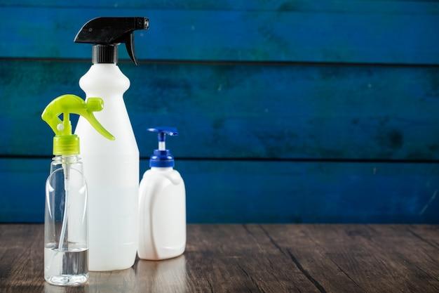 Desinfectantes para manos en contenedores blancos en la pared azul