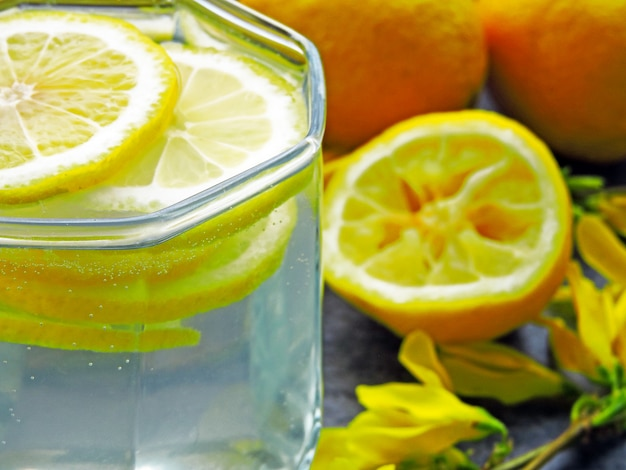 Desintoxica el agua con jugo de limón y flores amarillas en las ramas.