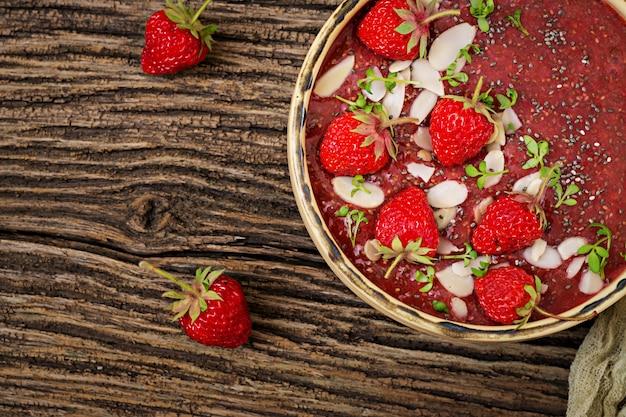 Desintoxicación y súper alimentos saludables desayuno en un tazón. budín vegano de semillas de chía con fresas y almendras. batido de fresas vista superior. lay flat