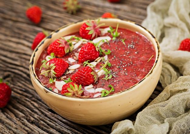 Desintoxicación y súper alimentos saludables desayuno en un tazón. budín vegano de semillas de chía con fresas y almendras. batido de fresas