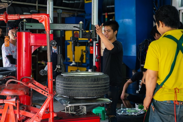 Desmontaje mecánico o técnico de automóviles no identificado y control de una rueda cromada de aleación de automóvil