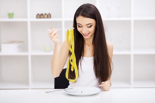 Desorden alimenticio. niña sostiene un plato y trata de poner un guisante en el tenedor