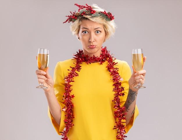 Desorientada joven rubia con corona de navidad y guirnalda de oropel alrededor del cuello sosteniendo dos copas de champán mirando a cámara aislada sobre fondo blanco