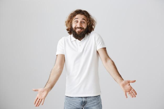 Desorientado apuesto hombre del medio oriente con barba larga, encogiéndose de hombros perplejo