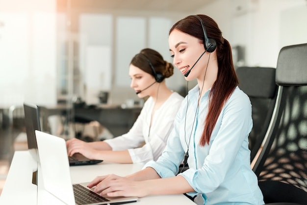 Despachador femenino atractivo respondiendo llamadas de negocios en la oficina de la empresa moderna