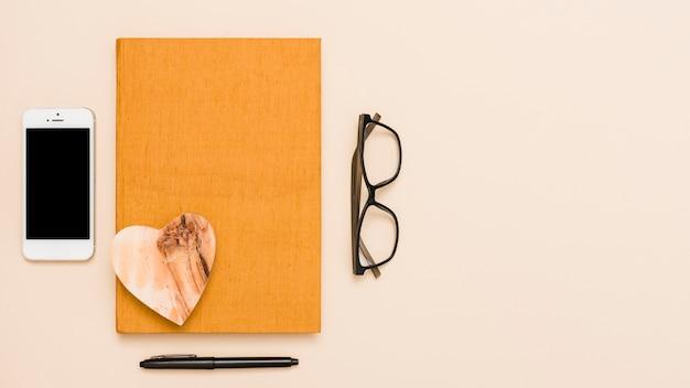 Despacho de oficina con libro, gafas y bolígrafo