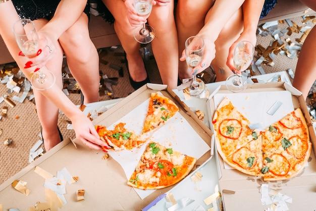 Despedida de soltera. foto recortada de chicas celebrando el próximo día especial de su amigo con pizza y vino espumoso.