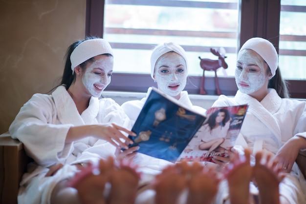 Despedida de soltera en el spa, chicas con mascarilla leyendo revistas