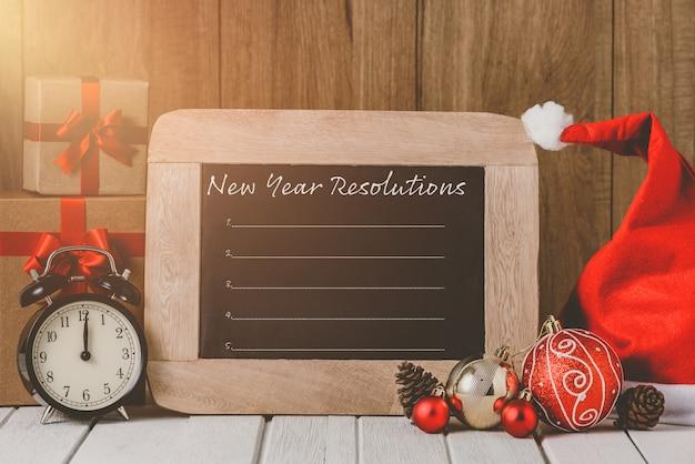 Despertador con adornos navideños y lista de resoluciones de año nuevo escrita en la pizarra