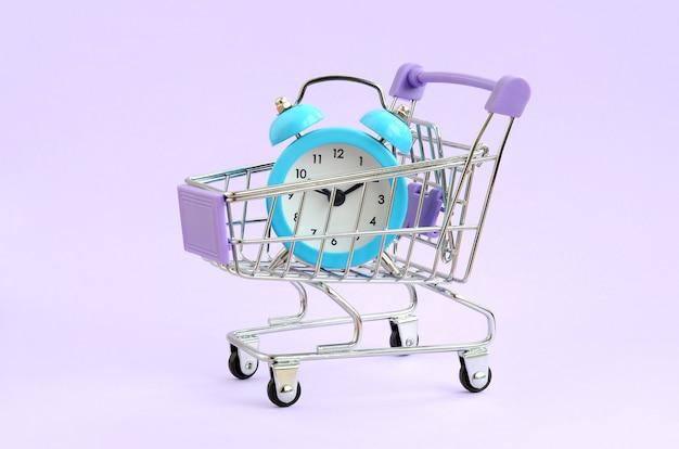 Despertador azul en carretilla del supermercado en el fondo violeta