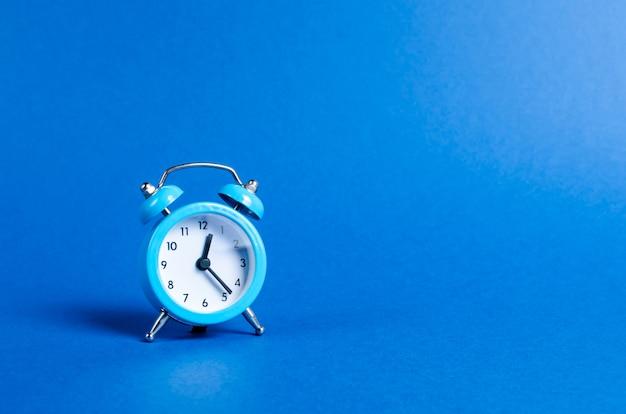 Un despertador azul sobre azul