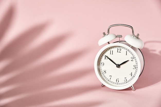 Despertador blanco y deja sombras sobre fondo rosa pastel. concepto de tiempo mínimo creativo