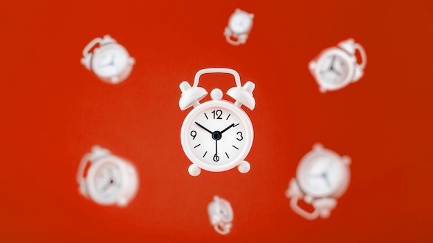 Un despertador blanco en levitación en el centro, aislado en un fondo rojo con un entorno de despertadores flotando en el fondo.
