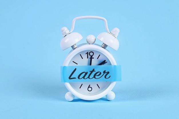 Despertador blanco con una nota adhesiva con texto más tarde.