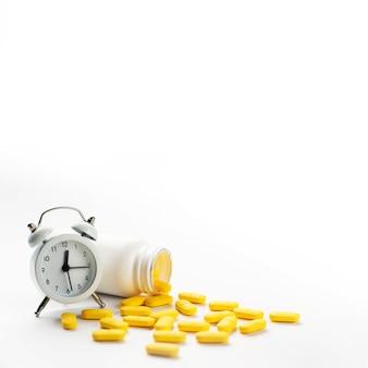 Despertador blanco y píldoras amarillas derramadas sobre fondo blanco.