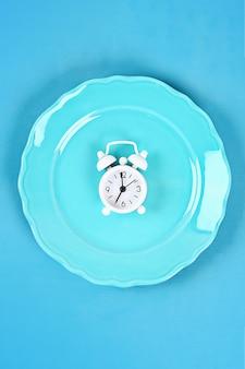 Despertador blanco en plato vacío azul.