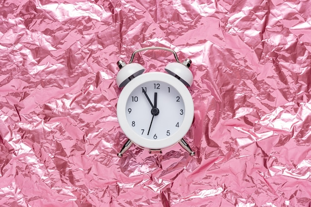 Despertador blanco sobre fondo rosa de papel arrugado.