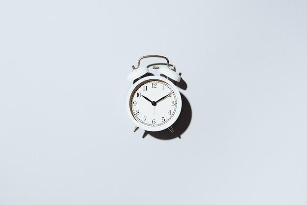Despertador blanco con sombra dura sobre fondo gris.