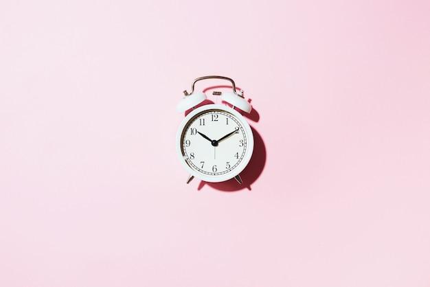 Despertador blanco con sombra dura sobre fondo rosa.