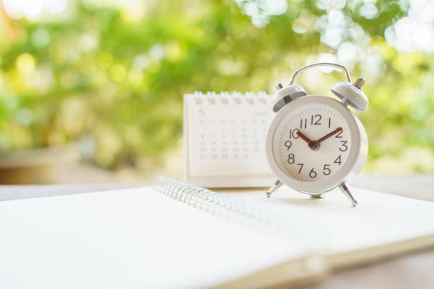 Despertador blanco vintage sobre madera. es hora de descansar. concepto de tiempo relajante