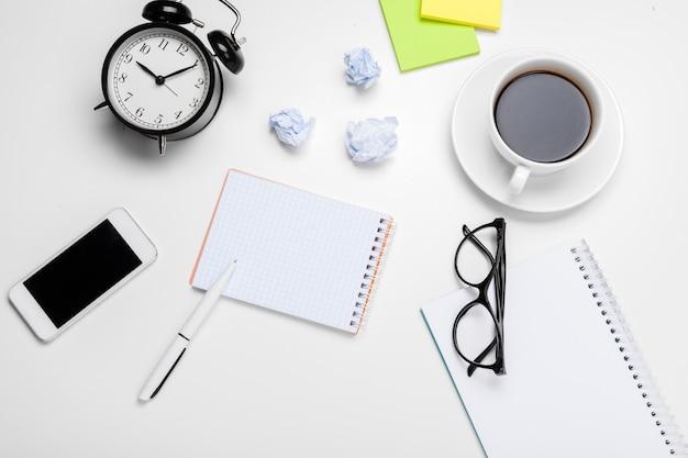 Despertador con bolas de papel arrugadas y útiles de oficina.