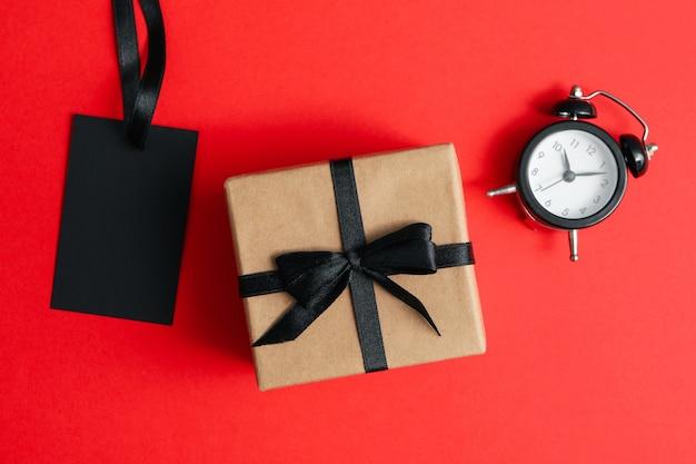 Despertador, caja de regalo y etiqueta en rojo.
