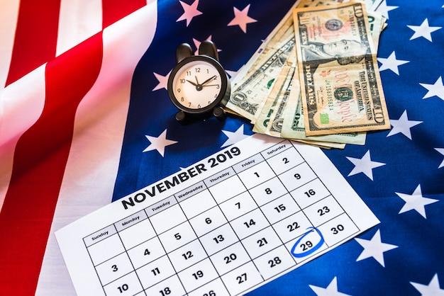 Despertador y calendario con 29 de noviembre de 2019, viernes negro, bandera estadounidense y dinero.