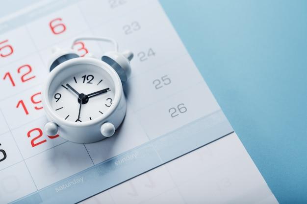 Despertador y calendario sobre un fondo azul.