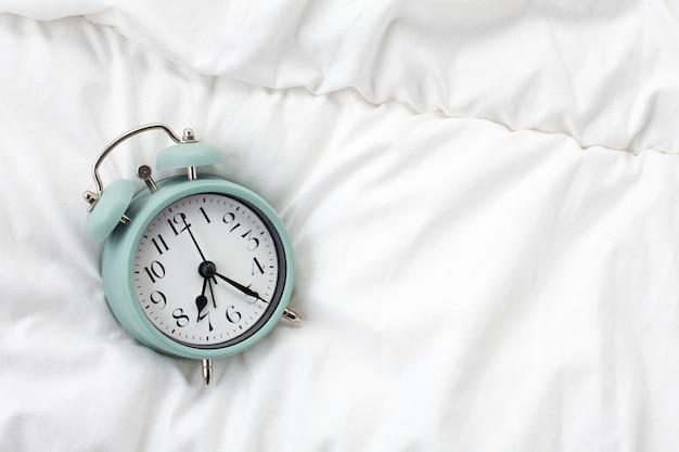 Despertador en la cama de la casa. tiempo de la mañana