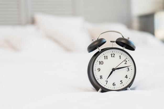 Despertador en cama con ropa blanca.