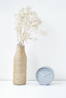 Despertador clásico y rama de flores en un florero, estilo minimalista