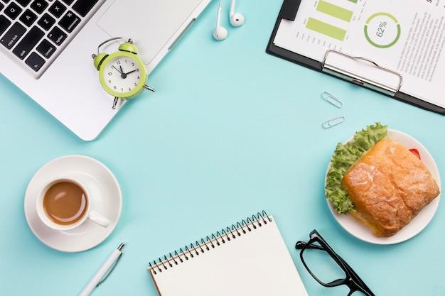 Despertador en computadora portátil, audífonos, bloc de notas en espiral, anteojos y plan de presupuesto sobre fondo azul