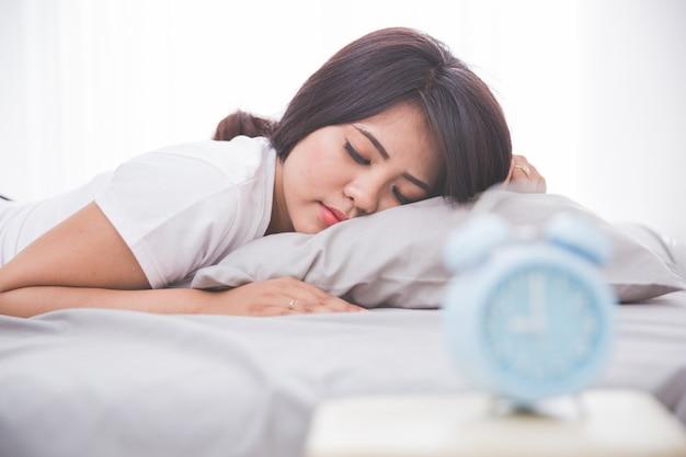 Despertador delante mujer durmiendo en una cama
