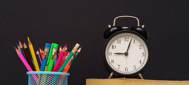 El despertador se encuentra en los libros y el vidrio con lápices en la pared negra.