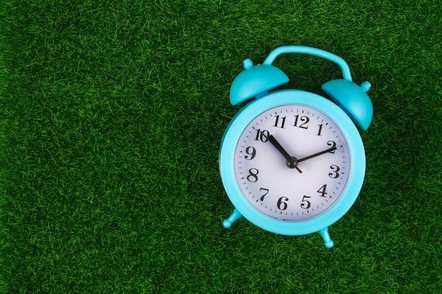 Despertador en el fondo de la hierba o del césped - concepto del tiempo.