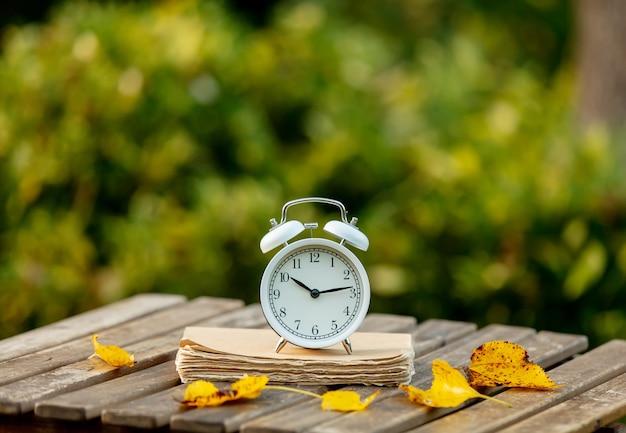 Despertador y un libro sobre una mesa en un jardín de otoño